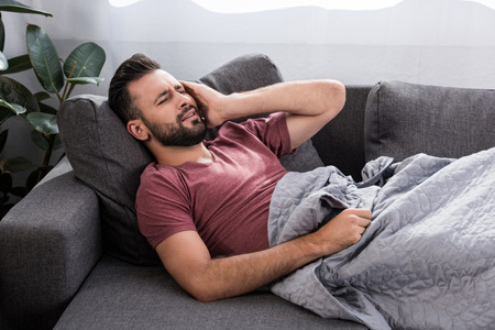 stuffering young man with headache lying on couch