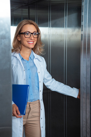 smiling attractive lecturer standing in elevator in medical university Stock Photo