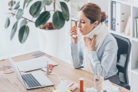 adult ill businesswoman with cough sitting at workplace in scarf