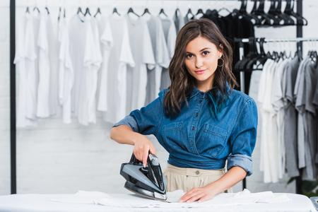 Sonriente joven diseñador planchando camiseta en estudio de diseño de ropa