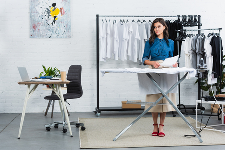 female fashion designer with painting for print on t-shirt standing near ironing board in clothing design studio Stock fotó