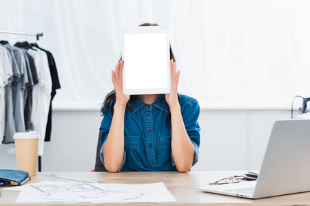young woman covering face by digital tablet with white blank screen Banque d'images - 110678008