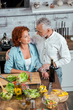 high angle view of husband hugging wife during salad preparation for dinner and they looking at each other 写真素材