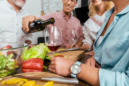 cropped image of handsome man pouring wine to happy old friends during dinner in kitchen Stok Fotoğraf