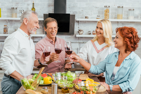 smiling old friends clinking with wineglasses in kitchen Stok Fotoğraf