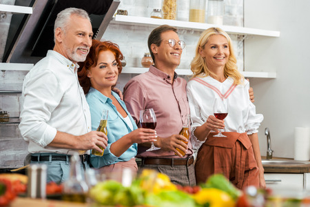 happy mature friends holding alcoholic beverages and looking away in kitchen Banco de Imagens