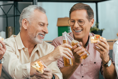 happy mature men eating pizza and clinking beer bottles at home