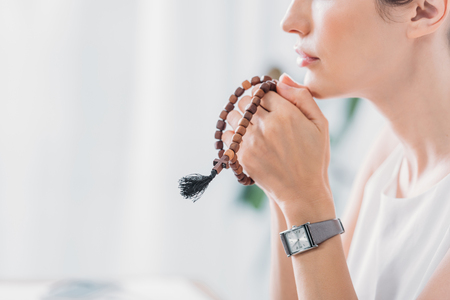 cropped view of woman praying with wooden rosary beads Stock Photo