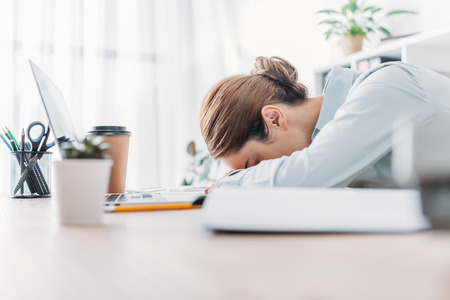 side view of overworked adult businesswoman sleeping at workplace