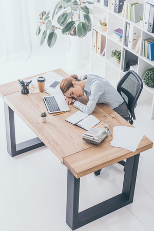 high angle view of overworked adult businesswoman sleeping at workplace