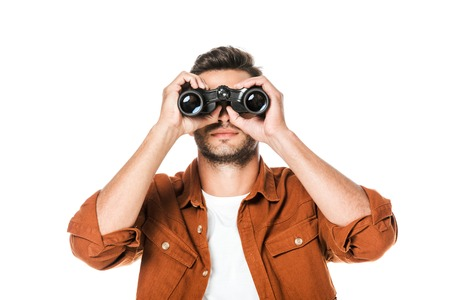 handsome young man looking at camera with binoculars isolated on white