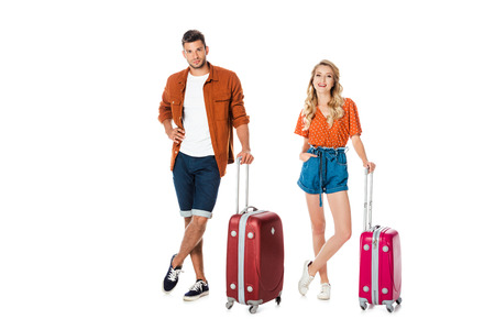 attractive young couple with suitcases looking at camera isolated on white