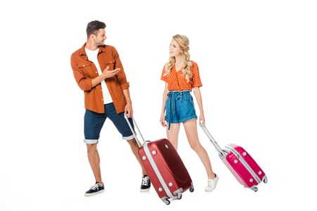 happy young couple with luggage walking and chatting isolated on white