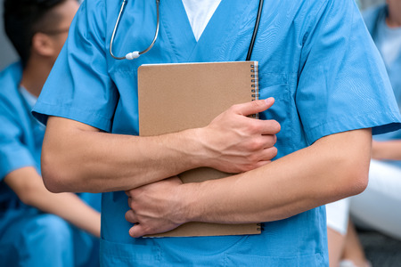 cropped image of medical student standing with notebook