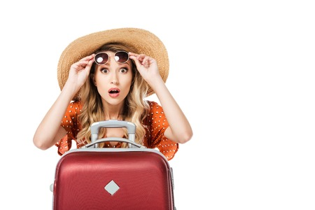 shocked beautiful girl holding sunglasses and sitting near travel bag isolated on white