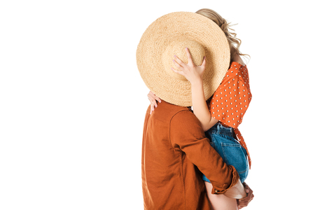 obscured view of couple cbehind straw hat isolated on white