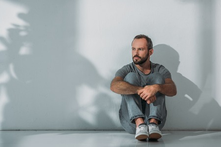 full length view of depressed bearded middle aged man sitting on floor and looking away Фото со стока