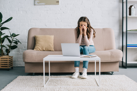 young woman with headache rubbing nose bridge while working with laptop at home 스톡 콘텐츠