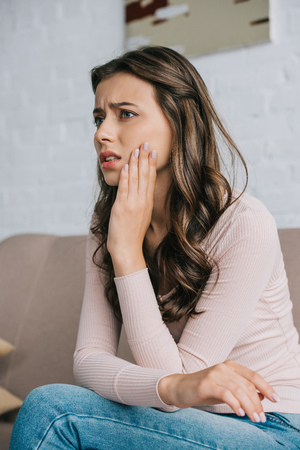 young woman suffering from jaw pain and looking away at home
