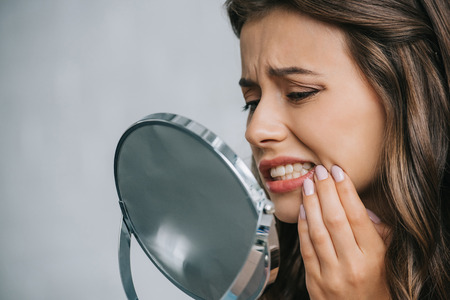 close-up view of young woman having toothache and looking at mirror Фото со стока