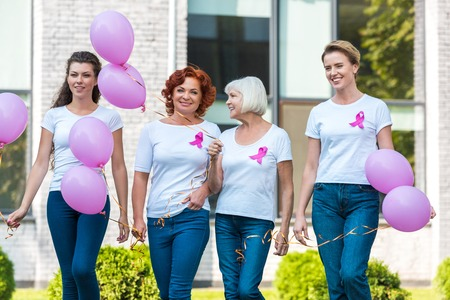 happy women holding pink balloons and walking together, breast cancer awareness concept Archivio Fotografico