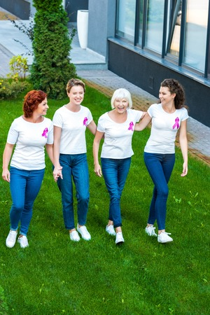 high angle view of four smiling women with breast cancer awareness ribbons walking together