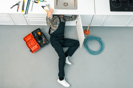 high angle view of plumber lying on floor, checking sink and taking tools in kitchen