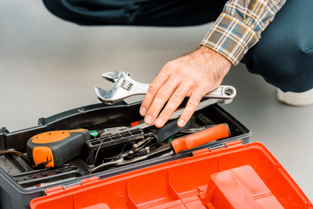 cropped image of plumber taking adjustable wrench from toolbox in kitchen Stock Photo