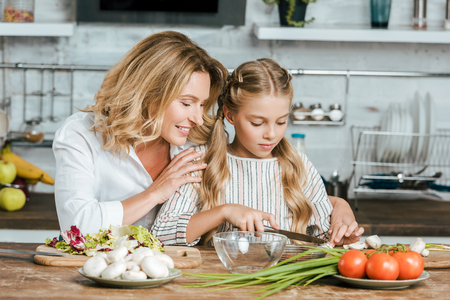 happy adult mother teaching her little daughter how to cook