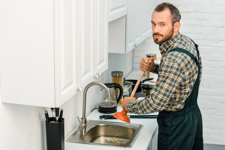 handsome plumber using plunger and cleaning sink in kitchen, looking at camera Foto de archivo - 110099367