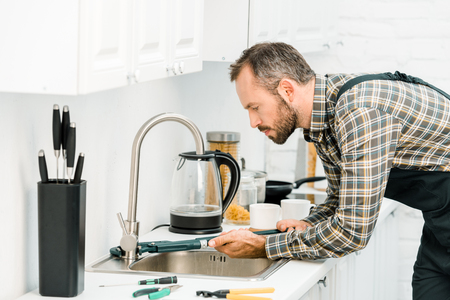 side view of handsome plumber repairing tap with monkey wrench in kitchen