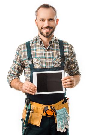 Fontanero sonriente guapo mostrando tableta con pantalla en blanco aislado en blanco
