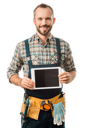 handsome smiling plumber showing tablet with blank screen isolated on white