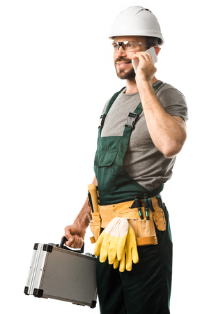 handsome electrician talking by smartphone and holding toolbox isolated on white Stok Fotoğraf