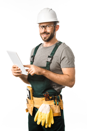 smiling handsome electrician in helmet and protective glasses using tablet isolated on white 免版税图像