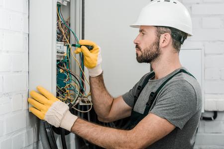 Seitenansicht eines gutaussehenden bärtigen Elektrikers, der den Elektrokasten repariert und einen Schraubendreher im Korridor verwendet