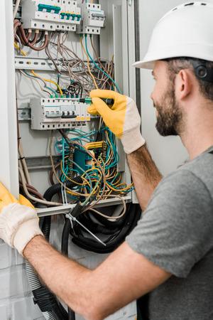 Seitenansicht des Elektrikers, der den Elektrokasten repariert und einen Schraubenzieher im Flur verwendet Standard-Bild