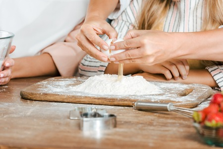 cropped shot of child and women breaking egg into flour for dough on rustic table Reklamní fotografie