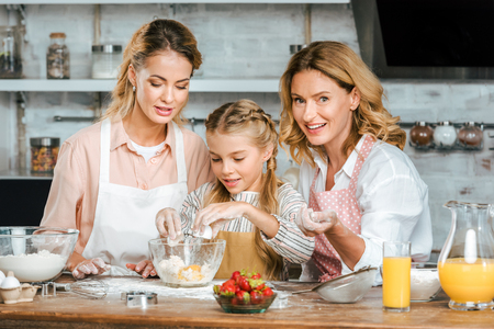 smiling beautiful child with mother and grandmother making dough together at home Stock Photo