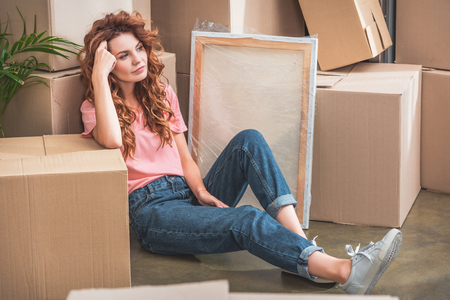 attractive woman with curly red hair in casual clothes sitting on floor near cardboard boxes at new home Stockfoto