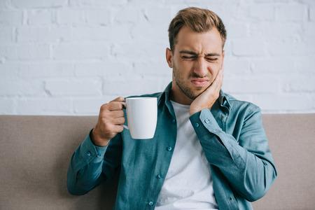 junger Mann, der eine Tasse hält und an Zahnschmerzen leidet