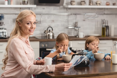 smiling mother having cup of coffee while sitting at kitchen with kids during breakfast and looking at camera Banco de Imagens