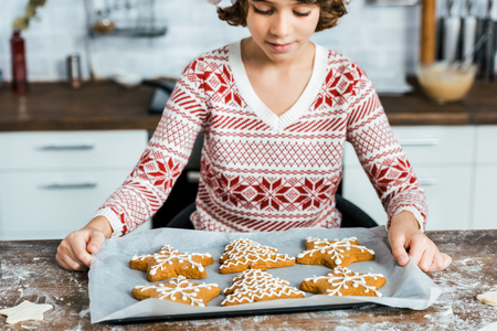 cropped shot of cute little boy holding baking tray with delicious christmas cookies Stock Photo
