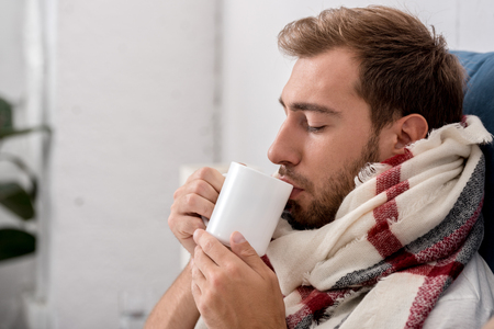 close-up portrait of diseased young man in scarf with cup of tea