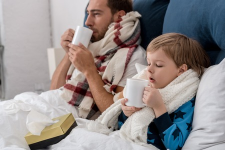 ill father and son in scarves with cups of hot drink sitting in bed