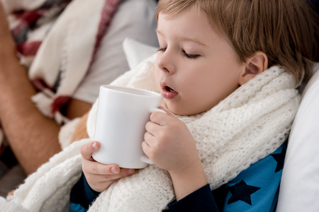 close-up portrait of little kid in scarf with cup of hot drink sitting in bed Stockfoto