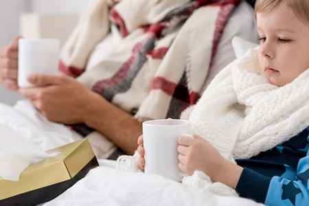 cropped shot of ill father and son in scarves with cups of hot drink sitting in bed Stockfoto - 111742433