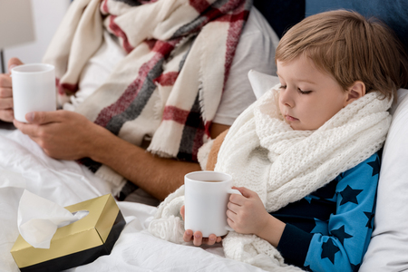 cropped shot of sick father and son in scarves with cups of hot drink sitting in bed Stockfoto - 111742435