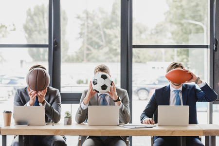 young office workers holding balls while working with laptops in office Stock Photo - 112349918
