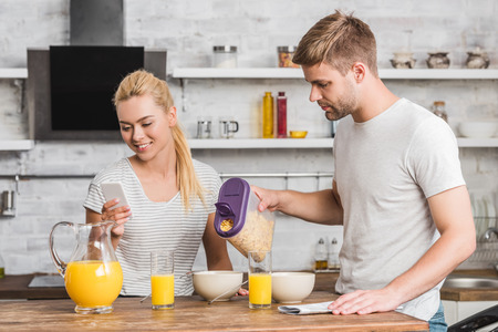 boyfriend pouring cornflakes into plate during breakfast in kitchen, girlfriend using smartphone